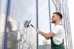 Reiniger, der Fensterglas mit Gummiwalze von der Außenseite abwischt Lizenzfreie Stockfotografie