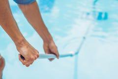 Reiniger des Swimmingpools Mann in einem blauen Hemd mit der Reinigungsanlage für Schwimmbäder, sonnig stockbilder