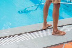 Reiniger des Swimmingpools Mann in einem blauen Hemd mit der Reinigungsanlage für Schwimmbäder, sonnig stockfotografie