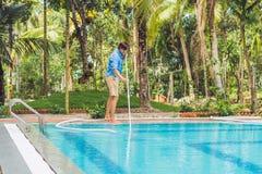 Reiniger des Swimmingpools Mann in einem blauen Hemd mit der Reinigungsanlage für Schwimmbäder, sonnig Lizenzfreie Stockfotos