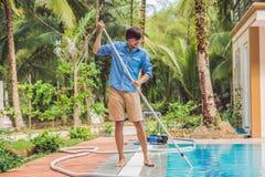 Reiniger des Swimmingpools Mann in einem blauen Hemd mit der Reinigungsanlage für Schwimmbäder, sonnig Lizenzfreie Stockfotografie