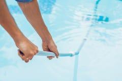 Reiniger des Swimmingpools Mann in einem blauen Hemd mit Reinigung lizenzfreies stockbild