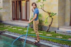Reiniger des Swimmingpools Mann in einem blauen Hemd mit Reinigungsanlage für Schwimmbäder Poolreinigungsdienstleistungen stockbild