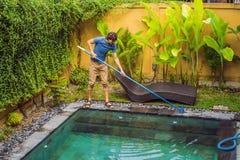 Reiniger des Swimmingpools Mann in einem blauen Hemd mit Reinigungsanlage f?r Schwimmb?der Poolreinigungsdienstleistungen stockbild