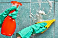 Reiniger macht Reinigung unter Verwendung eines Reinigungssprays für Badezimmer lizenzfreie stockfotos