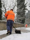 Reiniger schaufelt Schnee vom Bürgersteig nach den Schneefällen lizenzfreie stockbilder
