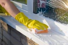Reiniger wäscht ein Fensterbrett draußen stockbilder