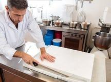Reinigung der französischen süßen Nugatspezialität durch Gebäckhandwerker Stockbilder