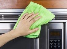 Reinigungs-Küchengerät-Entlüftungen auf Mikrowelle Stockbild