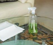 Reinigungs-Lösungs-Sprühflasche auf schmutzigen Glastisch Lizenzfreie Stockbilder