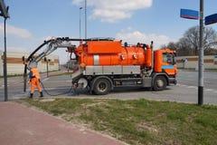 Reinigungsabwasserkanaleinsteigelöcher Arbeitskraft- und Spezialistenauto lizenzfreie stockfotografie
