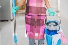 Reinigungsboden der jungen Frau mit Mopp und Eimer stockbild