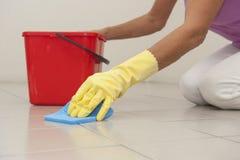 Reinigungsbodenfliesen mit Schwamm und Handschuh. Stockfotos
