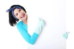 Reinigungsfrau, die unbelegten Zeichenvorstand zeigt. lizenzfreies stockbild