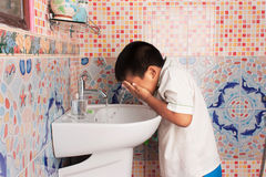 Reinigungsgesicht des Jungen im Badezimmer Lizenzfreie Stockfotografie