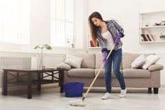 Reinigungshaus der jungen Frau mit Mopp stockbilder