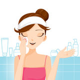Reinigungsmake-up der jungen Frau auf ihrem Gesicht Lizenzfreie Stockfotografie
