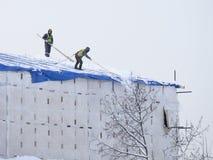 Reinigungsschnee auf dem Dach in Moskau