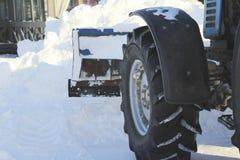 Reinigungsschnee von der Straße mit Planierraupe in der Stadt im Winter, im Fokus auf Blatt und im Rad Lizenzfreies Stockfoto