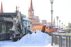 Reinigungsschnee von der Straße mit Planierraupe und LKW in der Stadt Stockfotografie