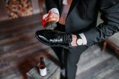 Reinigungsschuhe auf hölzernem Hintergrund schwarzer Schuh mit einer Bürste Stockbild