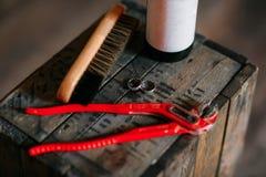 Reinigungsschuhe auf hölzernem Hintergrund schwarzer Schuh mit einer Bürste Justierbarer Schlüssel des Rotes Heller weißer Hinter Stockbilder