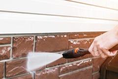Reinigungsservice-Reinigungsgeb?udefassade mit Druckwasser Schmutzige Reinigungswand mit Hochdruckwasserstrahl Energiewaschen lizenzfreies stockfoto