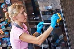 Reinigungsservice sauberer Kocher der Frau an der Küche Lizenzfreie Stockfotos