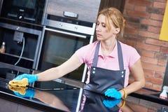 Reinigungsservice sauberer Kocher der Frau an der Küche Stockbilder