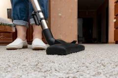 Reinigungsteppiche mit Staubsauger, Hausfrau, die ein VAC-Hauptprogramm verwendet lizenzfreie stockbilder