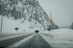 Reinli, Norwegen - 26. März 2018: Ansicht im Freien des Winterstraßenschnees und -eises im Wald, mit informativem Zeichen an Lizenzfreies Stockfoto