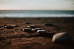 Reinsfjara Beach, Iceland. Some stones at a black sand beach in Iceland at sunset royalty free stock image
