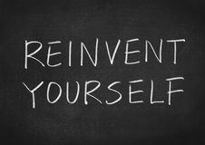 Reinvent yourself. Text on blackboard background Stock Photos