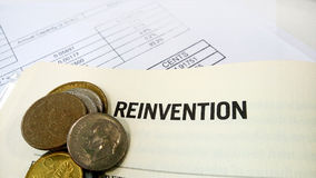 Reinvention word on the book with balance sheet Stock Images