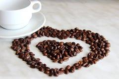 Reinweiß Tasse und Untertasse, viele Herz formte Kaffeebohnen stockfotografie