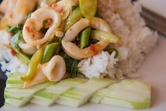 Reis überstieg mit angebratenem Kalmar und Basilikum auf der Platte Stockbilder