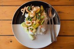 Reis überstieg mit angebratenem Kalmar und Basilikum auf der Platte Lizenzfreies Stockbild