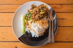 Reis überstieg mit angebratenem Schweinefleisch und Basilikum auf der Platte auf Holztisch Lizenzfreies Stockfoto