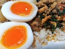 Reis überstieg mit angebratenem Schweinefleisch und Basilikum und Medium-kochte Ei lizenzfreies stockbild