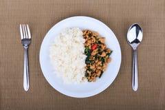 Reis überstiegen mit angebratenem Huhn und Basilikum, gebratener Aufruhrbasilikum mit gehacktem Huhn auf braunem Hintergrund Lizenzfreie Stockbilder