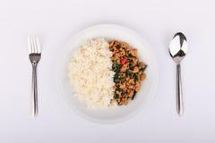 Reis überstiegen mit angebratenem Huhn und Basilikum, gebratener Aufruhrbasilikum mit gehacktem Huhn auf weißem Hintergrund Lizenzfreies Stockfoto