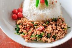 Reis überstiegen mit angebratenem Schweinefleisch und Basilikum Stockbilder