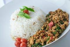 Reis überstiegen mit angebratenem Schweinefleisch und Basilikum Lizenzfreies Stockbild