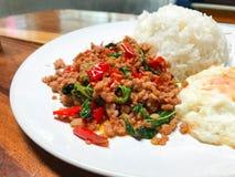 Reis überstiegen mit angebratenem Schweinefleisch und Basilikum Lizenzfreie Stockfotos