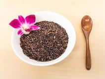 Reis-Beere mit hölzernem Löffel auf weißer keramischer Schüssel Stockfoto
