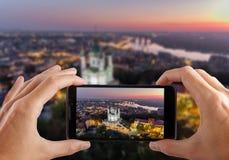 reis concept Handen die foto van St Andrew ` s Kerk Kiev de Oekraïne maken Cityscape van een hoogte stock afbeelding