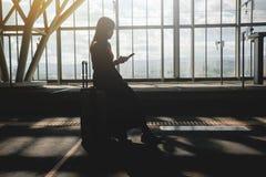 reis concept Jonge Vrouw die met Koffer op het Platform bij het Station wachten Het gebruiken van Smartphone om Tijdschema te con royalty-vrije stock foto