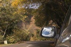 reis concept Mooie hemel en wolken in de spiegel van de sideviewauto op bergweg stock foto