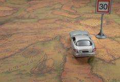 reis concept Stuk speelgoed auto op uitstekende Wereldkaart met verkeersteken royalty-vrije stock afbeeldingen