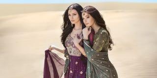 reis concept Twee gordeous vrouwenzusters die in woestijn reizen Arabische Indische filmsterren royalty-vrije stock foto's